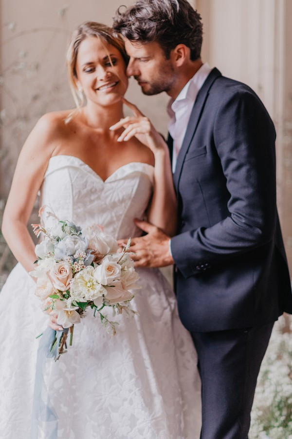 Bride and groom pose for the camera and look down at pastel bouquet