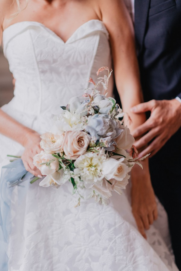 Groom touching arm of bride whilst she holds her pastel blue, cream and pink bouquet