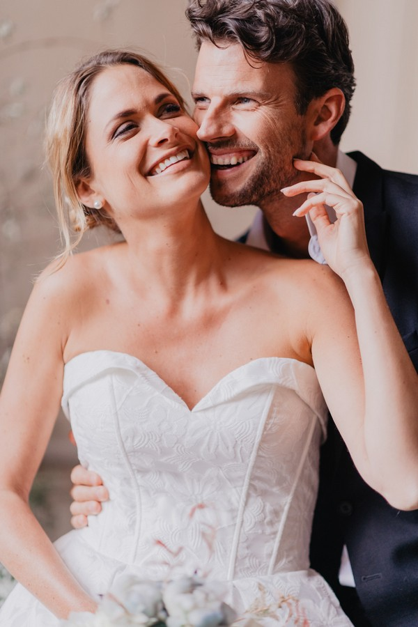 Bride and groom laugh at the camera and the bride touches her grooms face
