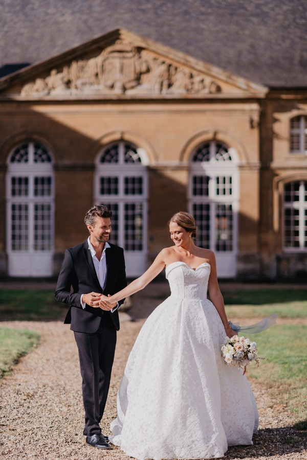 Bride and groom hold hands in the sun outside Chateau Cons La Grandville