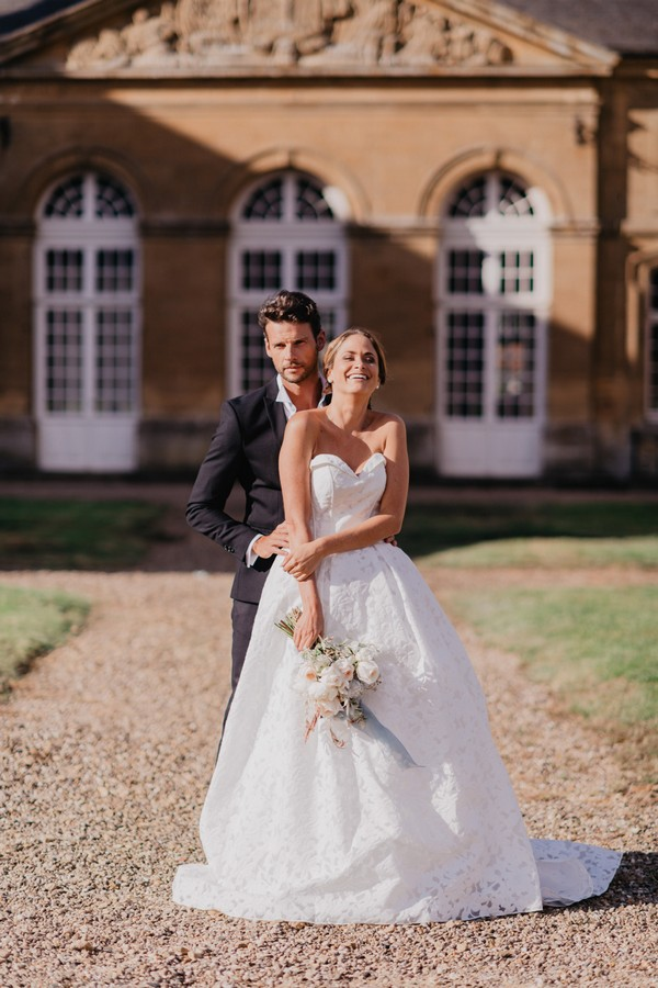 Bride and groom stand outside Chateau Cons La Grandville