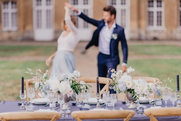 Bride and groom dance in the background behind blue themed wedding table with pastel flowers