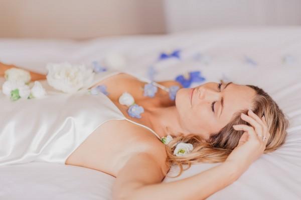 Bride sleeping amongst blue petals in white silk night gown