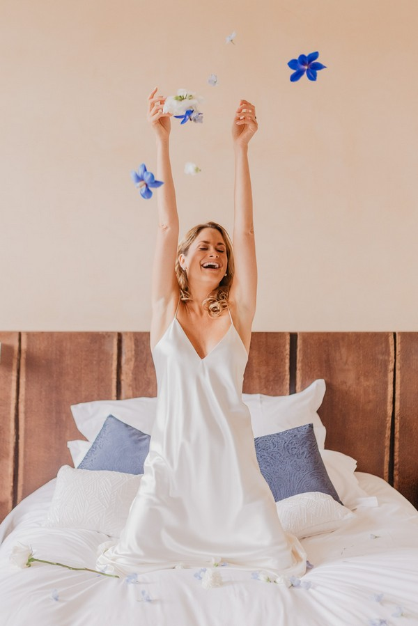 Bride on bed with arms in the air excited it is her wedding day