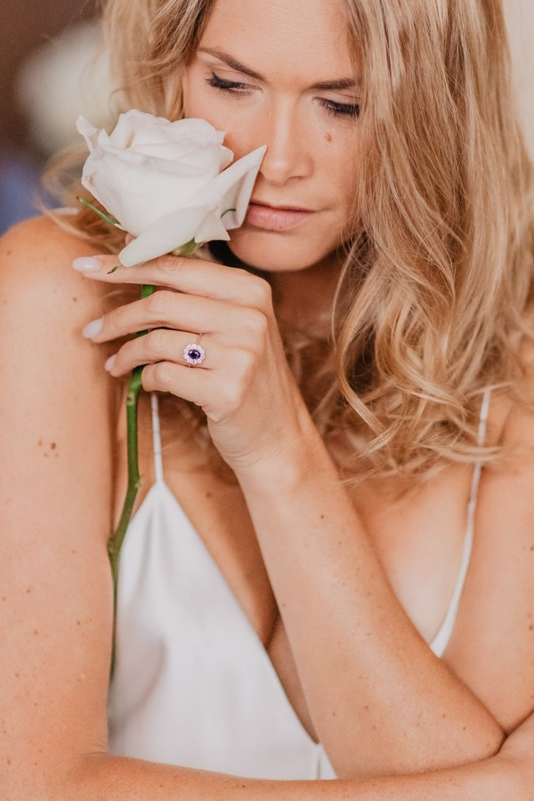 Bride in white silk nightie holds white rose to her nose