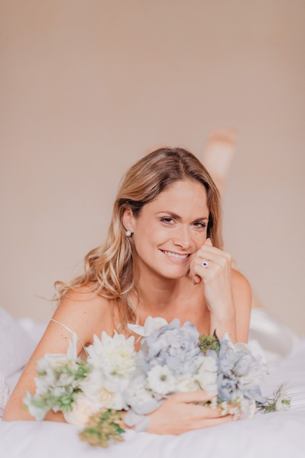 Bride laying on her stomach surrounded by blue flowers on the bed the morning of her wedding day