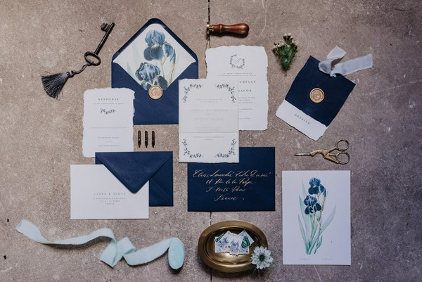 Flatlay of blue and white and gold wedding stationery with printed blue flowers