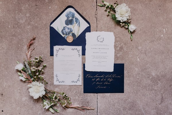 Flat lay of blue and cream wedding stationery with gold writing, gold wax seal and cream flowers