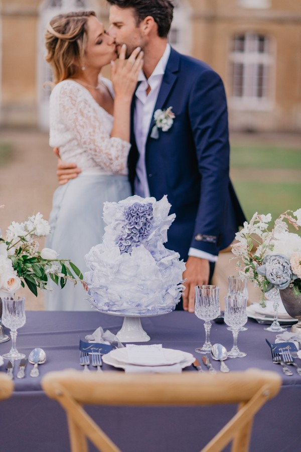Bride and groom kiss behind blue themed wedding table with blue ruffled wedding cake