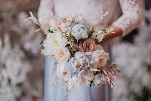 Pastel blue and pink bridal bouquet held by bride who fades into background