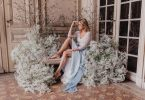 Bride in blue sitting amongs clouds of Baby's-breath flowers