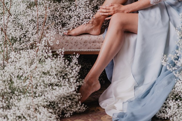 Brides feet and the bottom of her pale blue dress surrounded by clouds of Baby's-breath