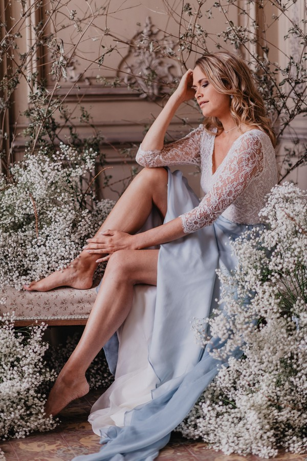 Barefoot Bride in pastel blue skirt and white lace top surrounded by Baby's-breath flowers