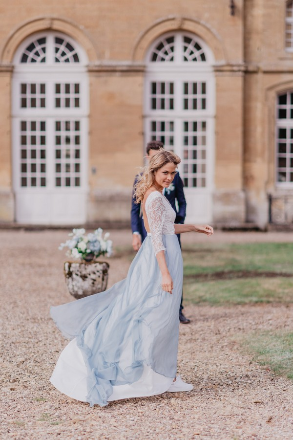 Bride's pale blue skirt trails behind her in the breeze as she walks toward her groom