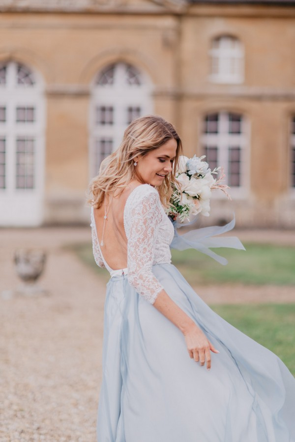 Bride spins her pale blue skirt outside Chateau Cons La Grandville
