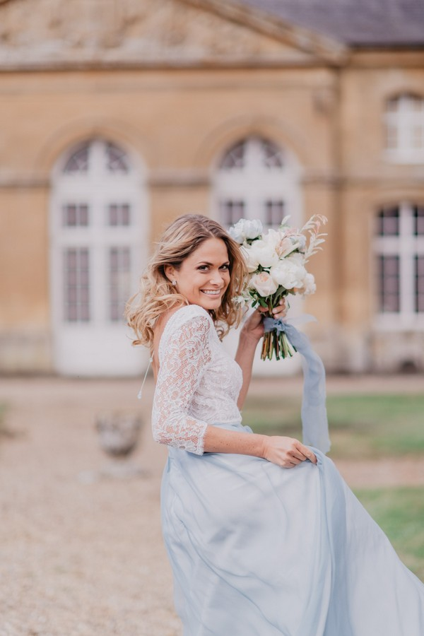 Bride in pastel blue skirt with white lace top holds bouquet wrapped in pale blue fabric to match her skirt