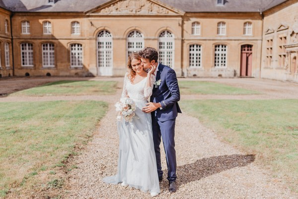 Bride in pale blue skirt and groom in midnight blue suit stand outside French Chateau