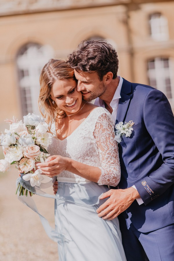 Bride and groom stand back to chest and kiss in the sunshine