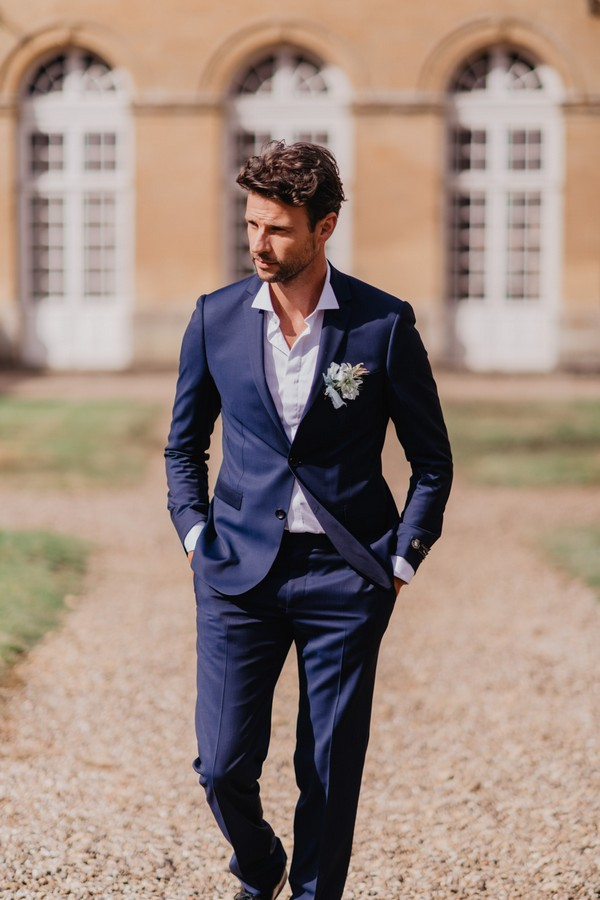 Groom in midnight blue suit with white buttonhole