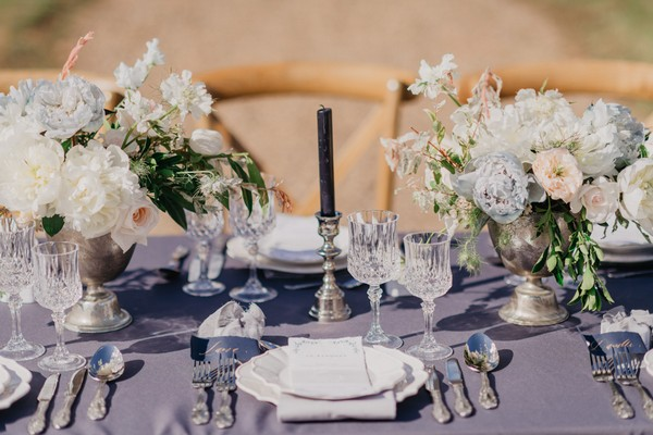 Wedding table setting with blue tablecloth, blue candles and pastel blue and cream floral arrangements