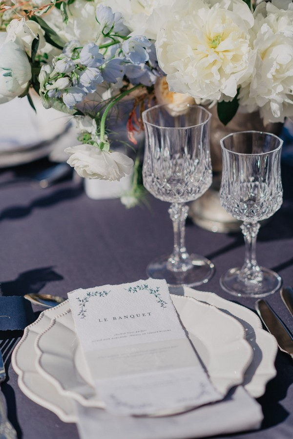 """Crystal goblets and cream and blue wedding stationery menu that reads """"Le Banquet"""""""