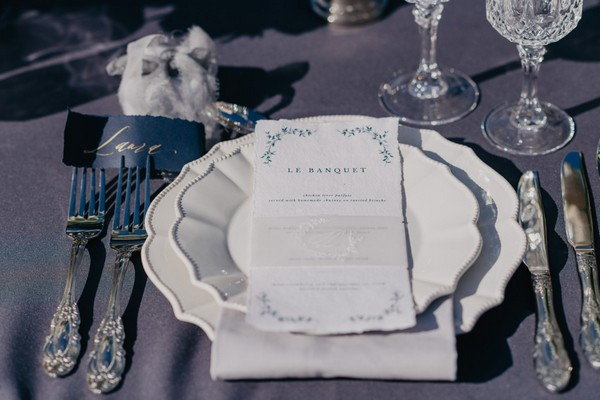 Wedding menu on white plate with silver cutlery and blue and gold nameplace holder