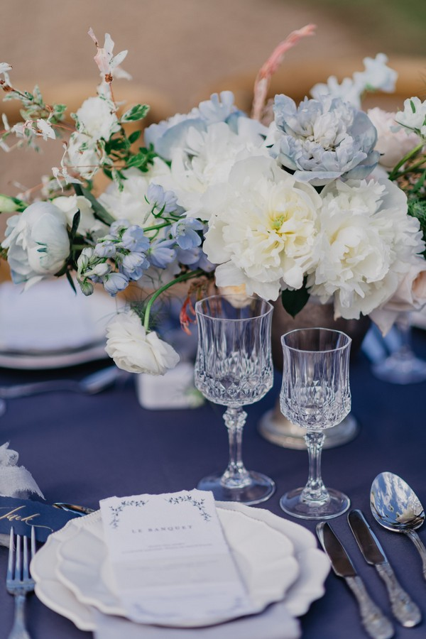 Blue floral arrangement on blue tablecloth with crystal glasses on wedding table