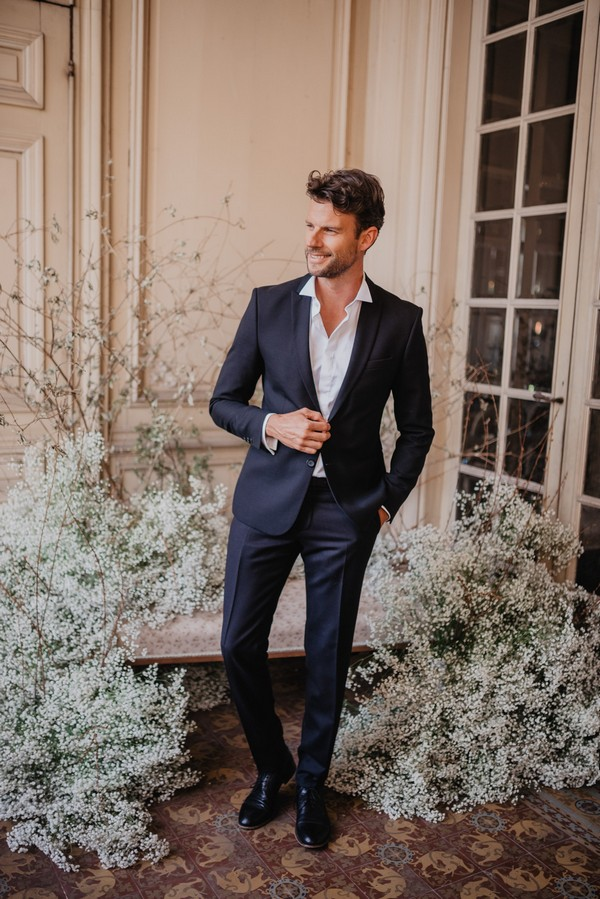Groom surrounded by Baby's-breath flowers wearing blue suit