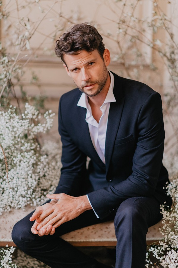 Groom in midnight blue suit and white unbuttoned shirt surrounded by white flowers