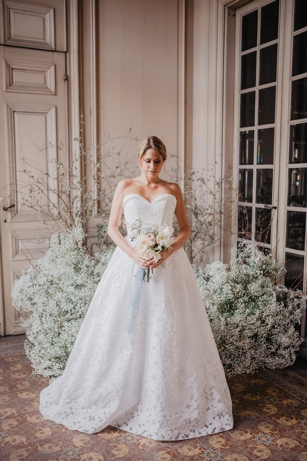 Bride surrounded by white Baby's-breath flowers in white strapless lace wedding gown
