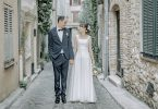 Bride and Groom stand in street of medieval town with stone buildings