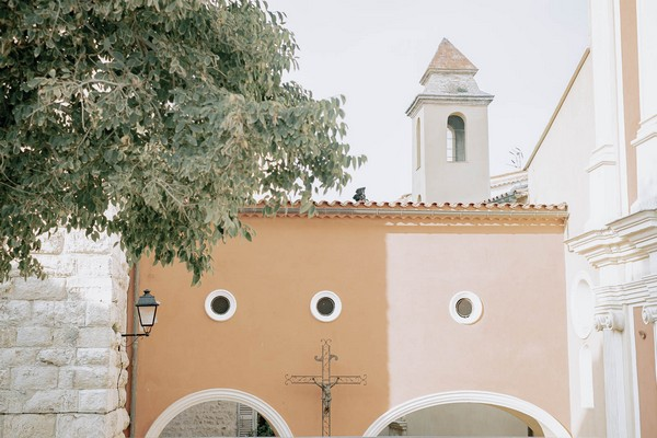 orange building with iron cross and white archways in Grasse, France