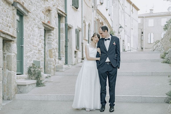 bride and groom stand in alleyway with stone buildings and green doors and shutters