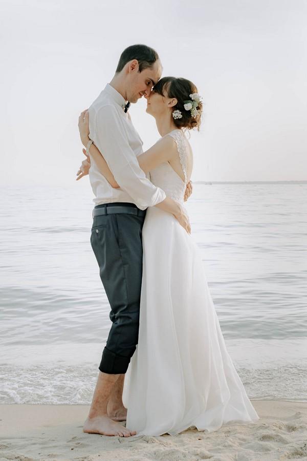 bride and groom barefoot in sand in front of ocean