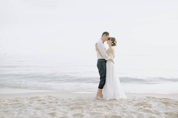 bride and groom barefoot in the sand embracing in front of ocean