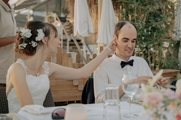 bride touches grooms ear seated at outdoor wedding table