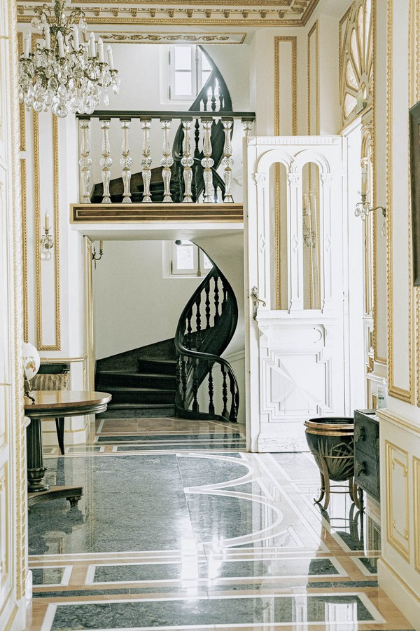 entrance hall of Chateau St George with black stone floors and white and gold trim doors and walls