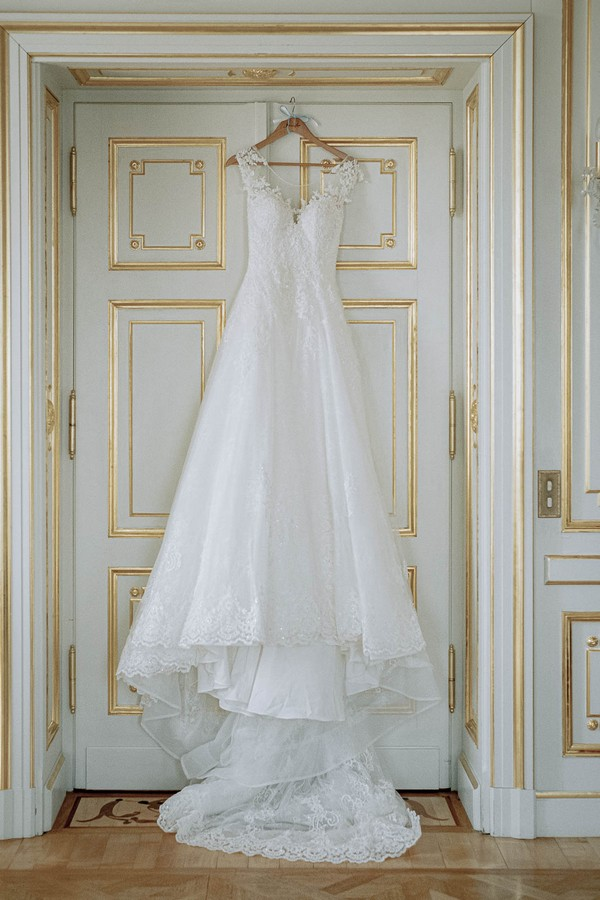 brides dress hangs from white and gold trim doorway