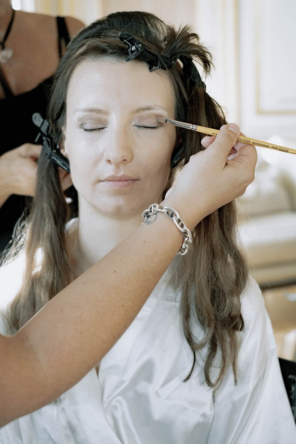 bride with eyes closed has hair and makeup applied