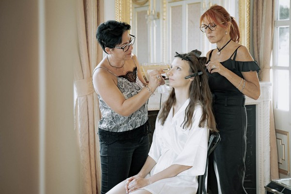 bride is seated looking toward ceiling with makeup artist and hair stylist getting her ready for her wedding