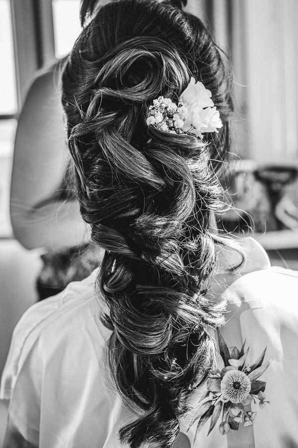 black and white image of brides completed hair style with white flowers