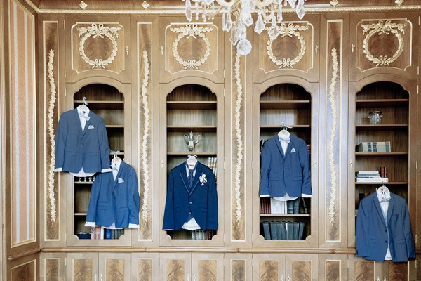 groom and groomsmen's blue suit jackets hand from wooden bookshelves