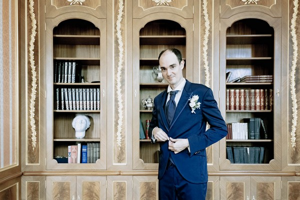 groom doing up jacket button in front of ornate bookshelves