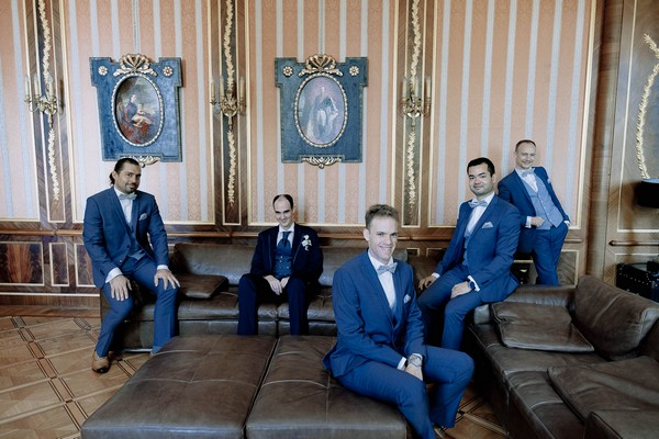 groom and groomsmen posed on brown leather lounges in front of ornate wallpaper and artworks