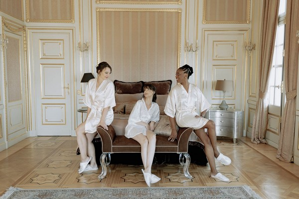 bride and her two bridesmaids seated on dressing bench in ornate chateau bedroom in silk robes and slippers