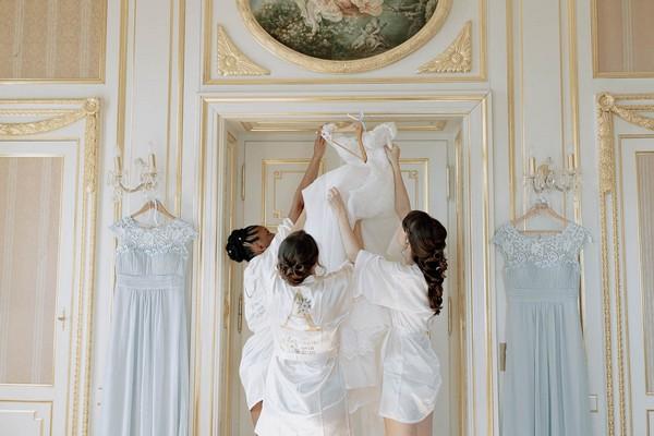 bride and bridesmaids take wedding gown down from hanger in door way