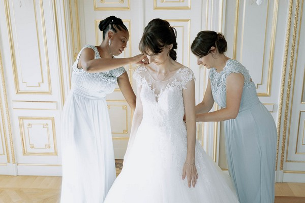 two bridesmaids in powder blue dresses help bride into her dress