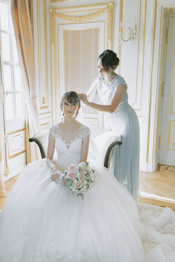 bridesmaid and sister to the bride helps her pin in her veil