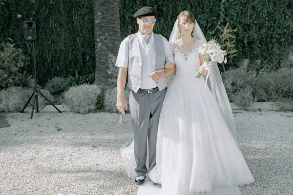bride being walked down outdoor aisle by man in waistcoat and beret