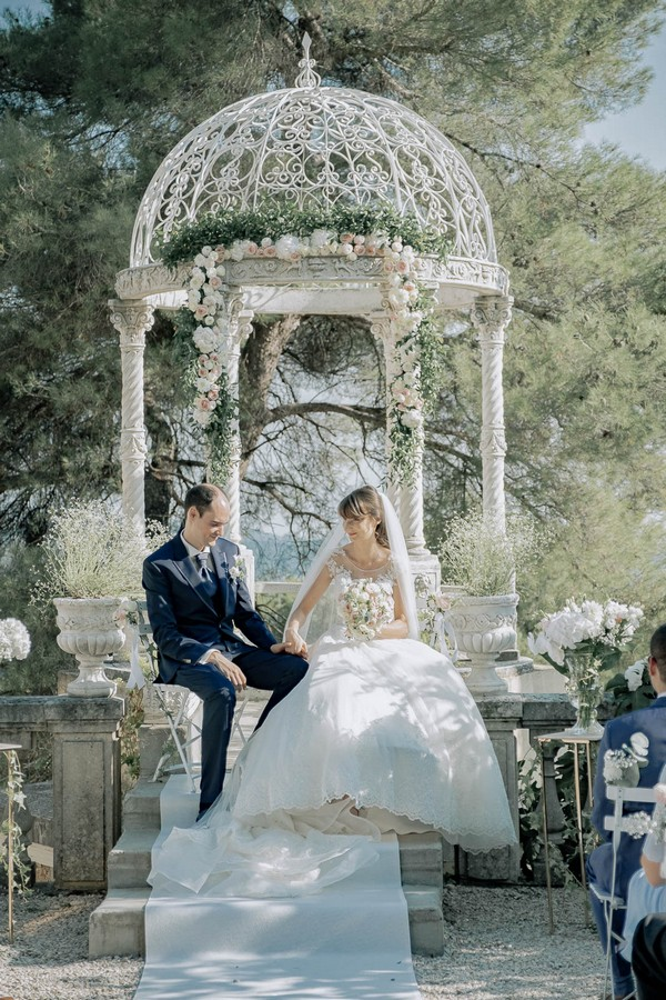 bride and groom sit in front of white ornate garden rotunda holding hands